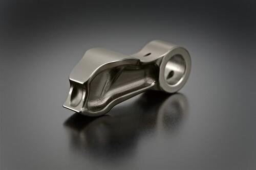 Questo è un bilanciere a dito della GSX-R, dotato di un riporto superficiale di DLC dello spessore di 2-3 micron soltanto. Ha una massa di 10 grammi (contro i 16 di una punteria a bicchiere del motore precedente), solo una parte della quale è in moto alterno