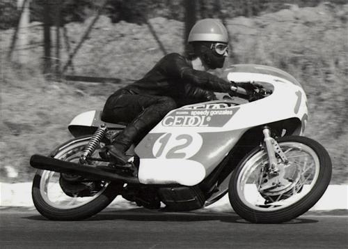 Siamo nel 1970, in una gara del campionato juniores. Sulla carena spicca la scritta della scuderia, ormai ben nota a tutti gli appassionati. Il pilota è Tarlazzi e la moto è una Ducati 250 a carter stretti, con freno anteriore Fontana a doppia camma