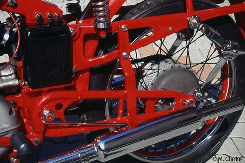 L'immagine mostra una tipica sospensione posteriore Sertum. Si possono osservare la particolare struttura dei bracci del forcellone oscillante, con gli ammortizzatori ad attrito vincolati alla estremità posteriore. La molla è una mezza balestra collocata verticalmente all'interno dell'elemento scatolato del telaio, a un lato del quale è fissata la batteria