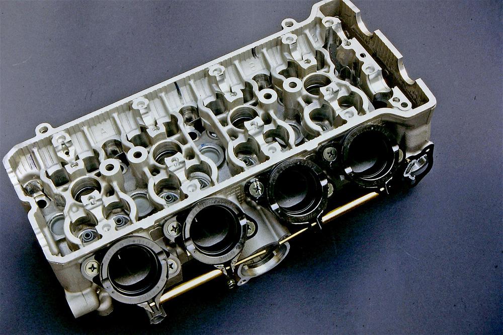 L'immagine dà una chiara idea della grande complessità delle teste dei moderni policilindrici. Si possono tra l'altro osservare i supporti per i due alberi a camme e gli alloggiamenti per le sedici punterie a bicchiere