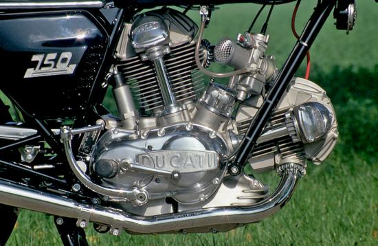 Nei primi bicilindrici a L della casa bolognese il comando della distribuzione, con un singolo albero a camme in ogni testa, era affidato a due alberelli ausiliari e a ben nove ingranaggi conici. Questo è il motore della 750 GT, entrata in produzione nel 1971