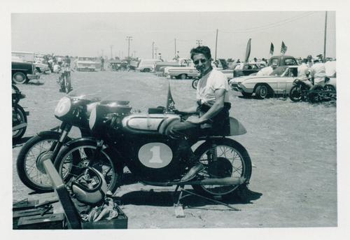 Norris Rancourt sulla Parilla 250 preparata da Orrin Hall di Sacramento, pressoché imbattibile nel 1962-63 (e seconda con Grant nel GP degli USA svoltosi a Daytona nel 1964). L'immagine, cortesemente fornita da Angelo Parilla, consente di osservare il paddock: uno spiazzo non asfaltato con vari pick-up e le moto…