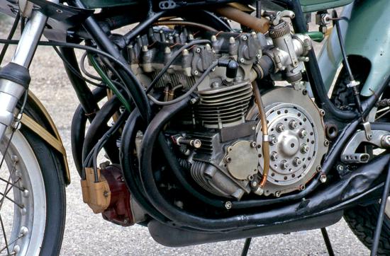 Vista di tre quarti del motore, a cilindri verticali, con in bella mostra il magnete d'accensione disposto anteriormente, in posizione centrale, e la grossa frizione a secco. Questa è l'ultima versione della moto, come si può notare dal disegno della parte anteriore del telaio
