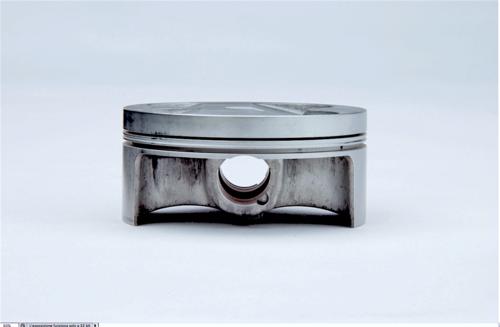 La foto mostra il pistone ad H di un moderno monocilindrico da cross. L'altezza è incredibilmente ridotta in relazione al diametro e il cielo è quasi perfettamente piano. Poiché è destinato a un motore da competizione i segmenti sono due soltanto