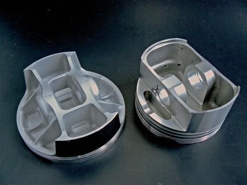 """I pistoni del tipo """"bridged"""" sono stati inizialmente sviluppati per le Formula Uno; oggi vengono impiegati su diversi motori motociclistici di altissime prestazioni. Qui uno di essi (a sinistra) è a confronto con un pistone di fine anni Ottanta"""