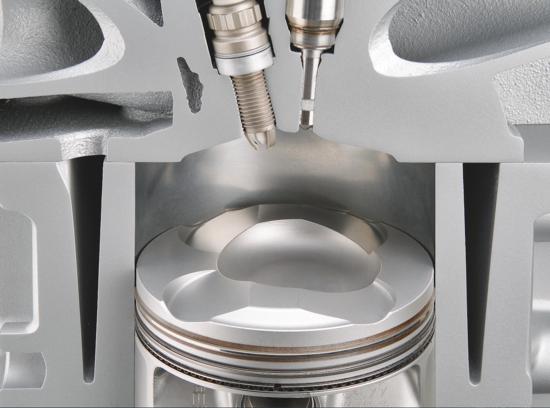 """La foto mostra la camera di combustione e il cielo del pistone di un motore BMW del 2005. Il sistema di iniezione è del tipo """"jet directed"""" ad alta precisione, con iniettore quasi verticale e collocato vicino alla candela. La forte atomizzazione del carburante necessaria viene ottenuta con una elevata pressione di iniezione"""