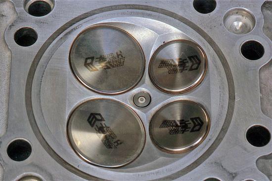 Camera di combustione a tetto di un motore di Formula Uno di 3000 cm3 dei primi anni Duemila. Le quattro valvole (in titanio) giacciono su due piani che formano un angolo assai ridotto (poco più di 20°) e la candela è in posizione centrale