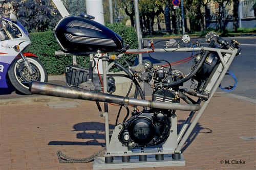 Vista laterale del motore installato nella struttura tubolare, con tanto di radiatore e di serbatoi del carburante e dell'olio, allestita per il montaggio sul banco prova. Si notino i tamponi in gomma piazzati inferiormente